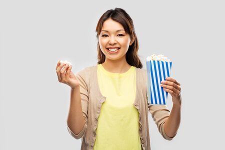Fast food and people concept - smiling Asian woman eating popcorn from striped bucket over grey background