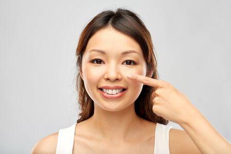 Schönheits- und Menschenkonzept - glückliche lächelnde junge Asiatin, die ihr Gesicht berührt