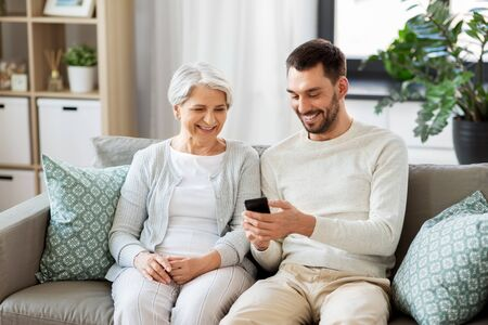 Family, generation and people concept - happy smiling senior mother and adult son with smartphone networking at home Banco de Imagens