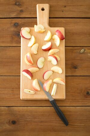 Sliced apples and knife on wooden cutting board