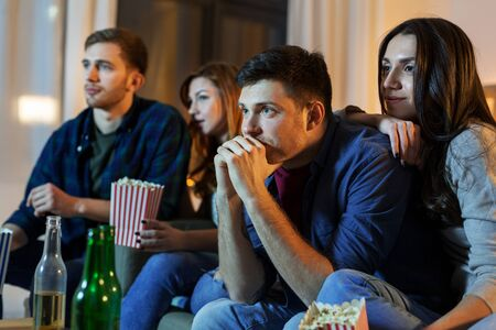 Friendship and leisure concept - friends with beer and popcorn watching tv at home at night Standard-Bild