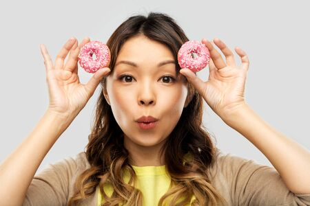 Happy Asian woman with donuts Banco de Imagens
