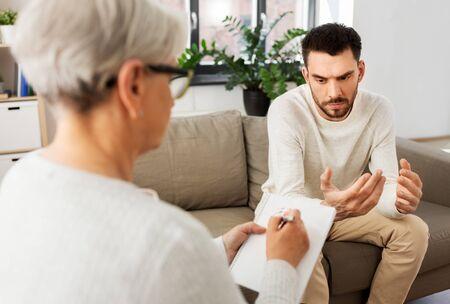 Senior woman psychologist and sad man patient