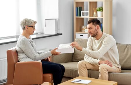 Senior psychologist giving tissues to man patient Stock Photo