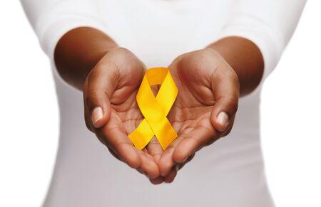 Kobiece ręce trzymające żółtą złotą wstążkę świadomości raka
