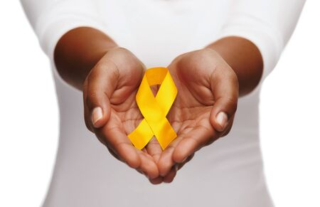 Woman's hands holding yellow gold cancer awareness ribbon