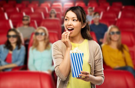 Asian woman eating popcorn at movie theater