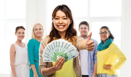 Asian woman with money showing thumbs up 스톡 콘텐츠