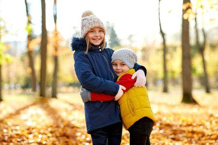 Enfants heureux étreignant au parc d'automne Banque d'images