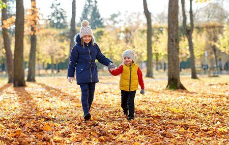 Happy children walking at autumn park