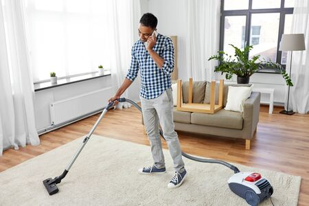 Man with vacuum cleaner calling on cell at home Reklamní fotografie