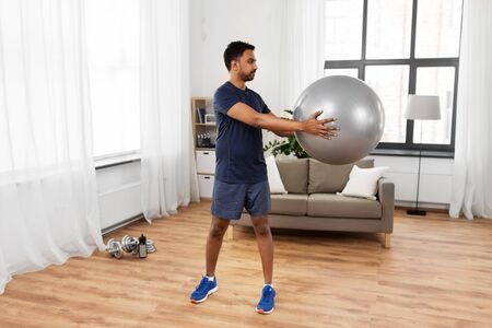 Indian man exercising with fitness ball at home Stock Photo - 126006194