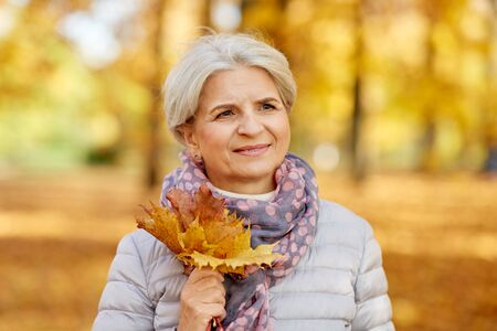 Senior woman with maple leaves at autumn park