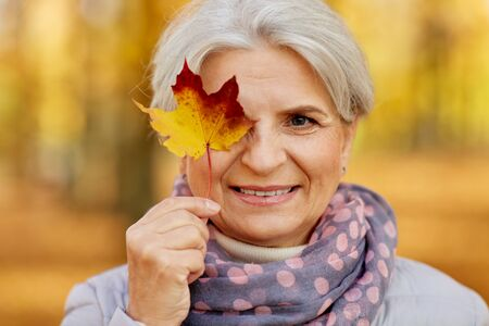 Happy senior woman with maple leaf at autumn park