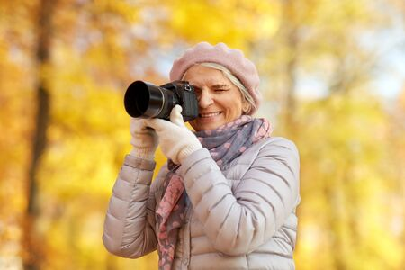 Senior woman with photo camera at autumn park