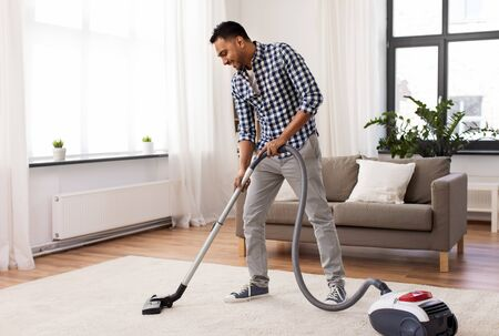 Indian man with vacuum cleaner at home