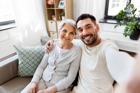 Ältere Mutter mit erwachsenem Sohn, der zu Hause selfie macht Standard-Bild
