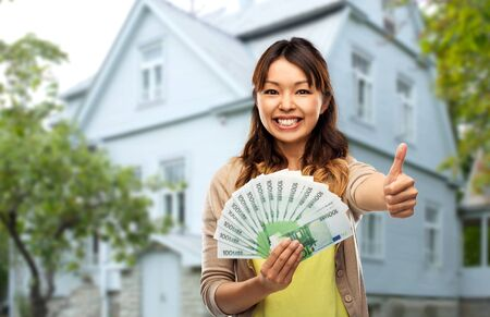 Asian woman with euro money showing thumbs up Stock Photo