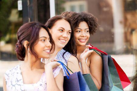 Mujeres felices con bolsas de compras en la ciudad de