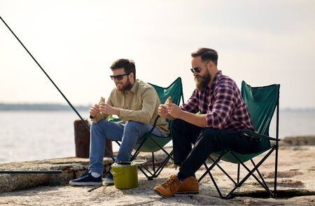 Happy friends fishing and eating sandwiches Stock Photo