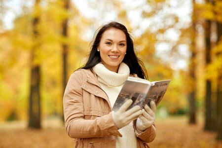 Happy young woman with city guide in autumn park