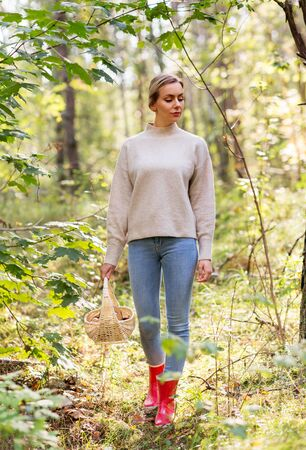 Season and leisure people concept - young woman with mushrooms in wicker basket walking in forest
