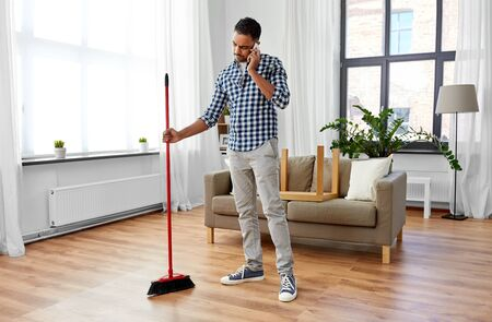 Hombre con escoba limpiando y llamando a smartphone Foto de archivo