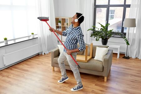 Man with broom cleaning and having fun at home Stockfoto