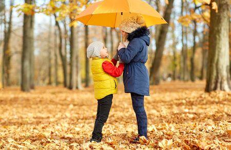 Happy children with umbrella at autumn park Foto de archivo