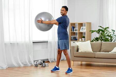 Indian man exercising with fitness ball at home Stock Photo - 126163046
