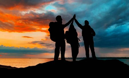 travel, tourism and hike concept - group of travelers with backpacks making high five over sunset background