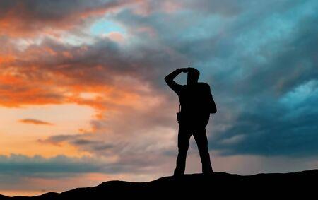 Concepto de viaje, turismo, caminata y personas: viajero con mochila de pie en el borde de la colina y mirando a lo lejos sobre el fondo del atardecer
