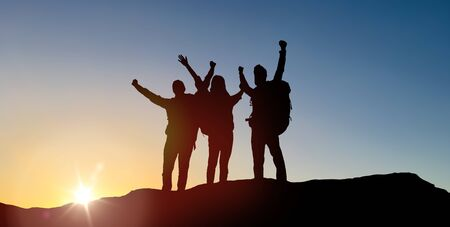 travel, tourism and hike concept - group of travellers with backpacks on mountain top over sunrise background