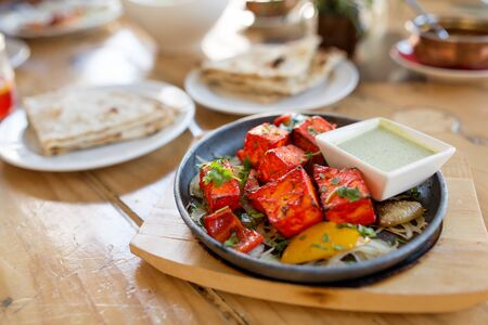 close up of paneer tikka dish with sauce on table