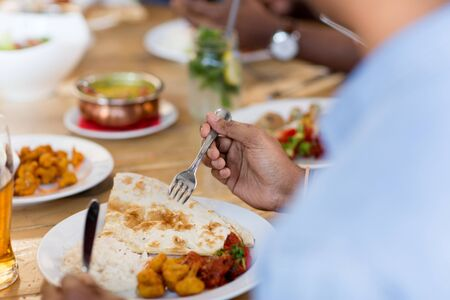 african man eating with friends at restaurant Stock Photo