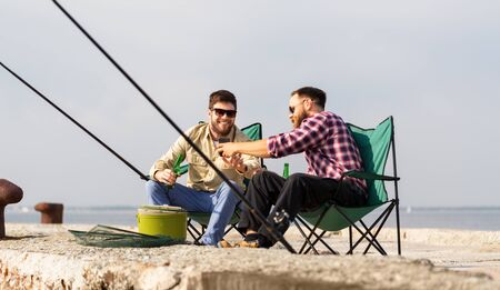 friends with smartphone fishing and drinking beer