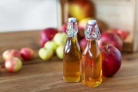 bottles of apple juice or vinegar on wooden table