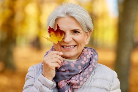happy senior woman with maple leaf at autumn park Stock Photo