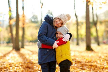 niños felices abrazándose en el parque de otoño