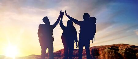 travel, tourism and hike concept - group of travellers with backpacks making high five over sunrise at grand canyon national park background Stock fotó
