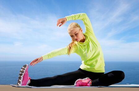 fitness, sport and healthy lifestyle concept - woman stretching on exercise mat over sea background
