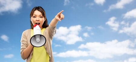 communication, feminism and human rights concept - asian young woman speaking to megaphone over blue sky and clouds background