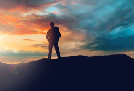 travel, tourism, hike and people concept - traveller with backpack standing on edge of hill over sunset background 版權商用圖片