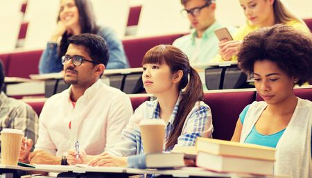 koncepcja edukacji, liceum, uniwersytetu, nauki i ludzi - grupa międzynarodowych studentów z zeszytami i kawą w sali wykładowej