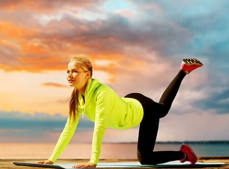 fitness, sport and healthy lifestyle concept - woman training on exercise mat over sea sunset background Stockfoto