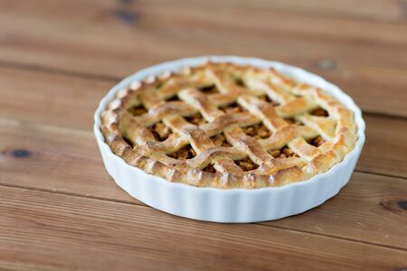 food, culinary and baking concept - apple pie on wooden table