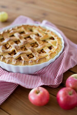 food, culinary and baking concept - apple pie and kitchen towel on wooden table 스톡 콘텐츠