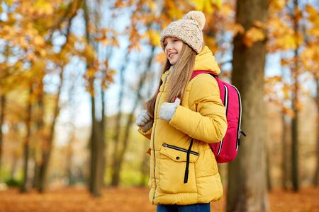school, education and season concept - happy student girl with schoolbag at autumn park