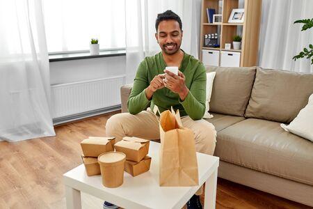 Indiase man die afhaalmaaltijden thuis controleert Stockfoto