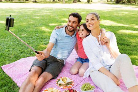 familia haciendo un picnic y tomando selfie en el parque